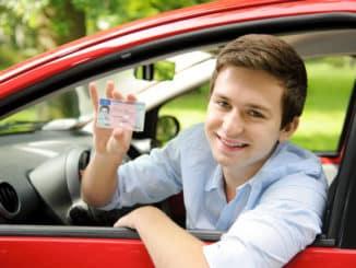 Junger Mann im Auto zeigt Führerschein